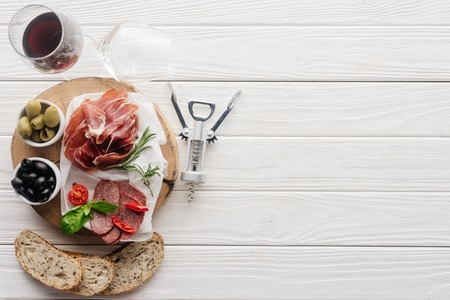flat lay with glass of red wine, pieces of bread and assorted meat snacks on white wooden tabletop