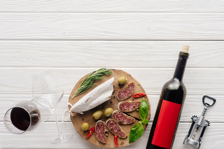 top view of bottle and glass of red wine with assorted meat appetizers on white wooden surface
