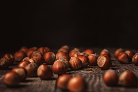 close up view of hazelnuts on wooden surface on black background Stockfoto