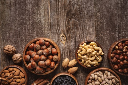 top view of nuts in bowls arranged on wooden tabletop 写真素材