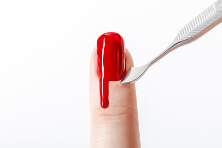 cropped view of woman using manicure instrument on fingernail with red nail polish isolated on white Фото со стока