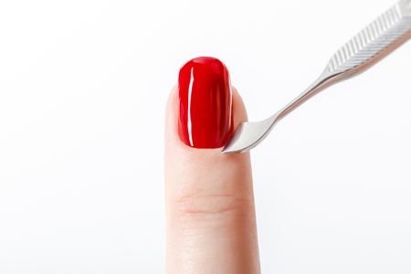 bright red nail polish on fingernail with cuticle pusher isolated on white
