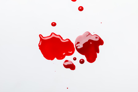 top view of red spilled  nail polish isolated on grey
