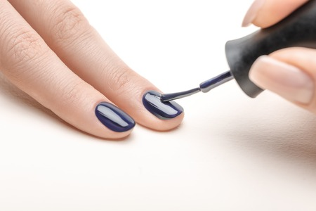 female manicurist applying navy blue nail polish on fingernail of woman on white background Stockfoto