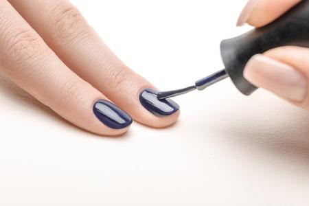weibliche Maniküre, die marineblauen Nagellack auf den Fingernagel der Frau auf weißem Hintergrund aufträgt