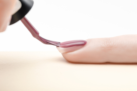 manicurist applying purple nail polish on fingernail of woman on white background
