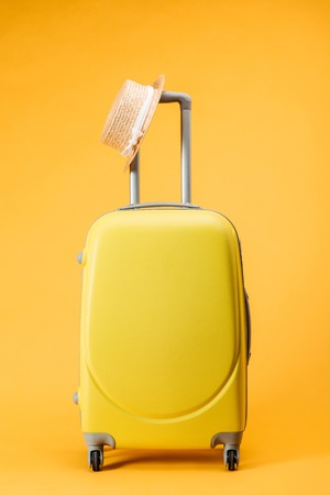 travel bag with wheels and straw hat on yellow background