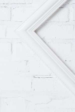 close up view of inclined white empty frame hanging on brick wall