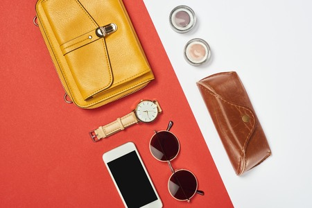 Vista superior del bolso, gafas de sol, sombra de ojos, teléfono inteligente, reloj y estuche. Foto de archivo