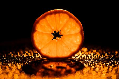 slice of orange on black background with bokeh and backlit 版權商用圖片