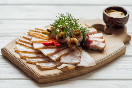 traditional tasty sliced smoked lard with dill, chilli pepper and mustard on cutting board with white wooden background Фото со стока