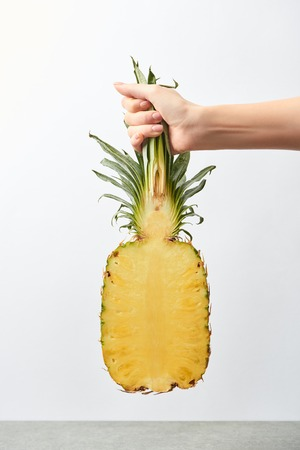 cropped view of woman holding yellow pineapple half in hand isolated on white