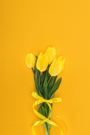 top view of yellow tulip bouquet with ribbon on orange background Imagens