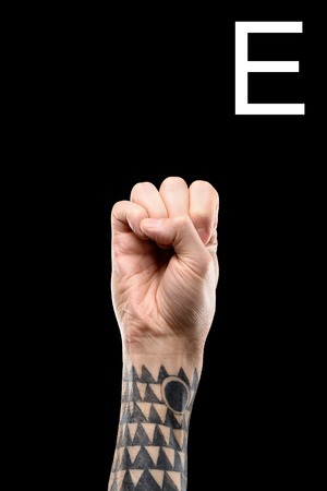 tattooed male hand showing latin letter - E, sign language, isolated on black