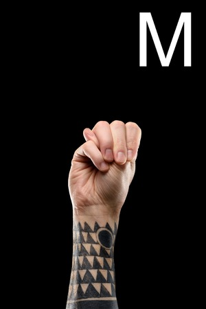 cropped view of tattooed hand showing latin letter - M, sign language, isolated on black Stock Photo
