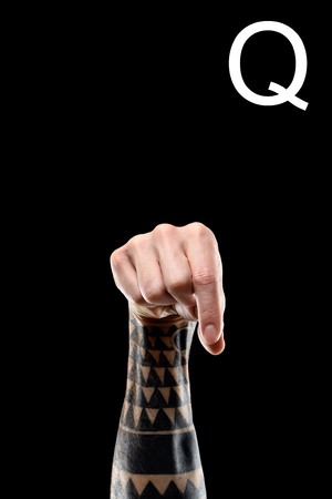 cropped view of tattooed hand showing latin letter - Q, deaf and dumb language, isolated on black