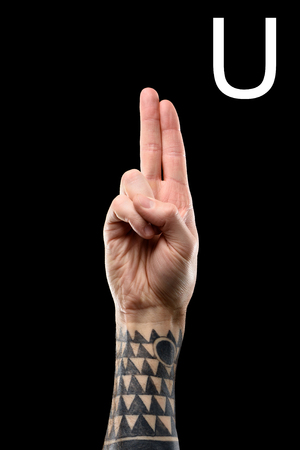 cropped view of tattooed male hand showing latin letter - U, deaf and dumb language, isolated on black Banco de Imagens