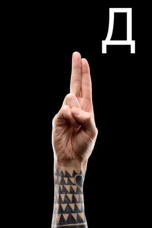 Deaf and dumb language with tattooed male hand and cyrillic letter, isolated on black