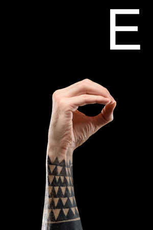 Cropped view of tattooed male hand showing cyrillic letter, deaf and dumb language, isolated on black