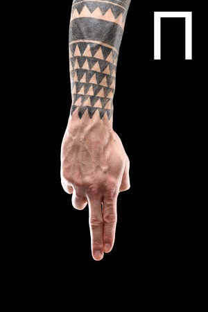 partial view of tattooed hand showing cyrillic letter, deaf and dumb language, isolated on black