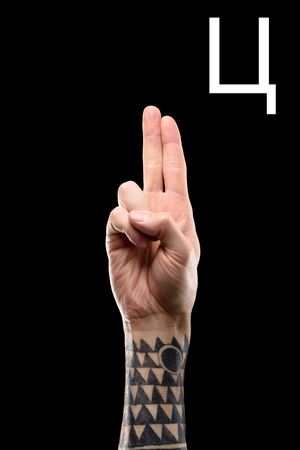 tattooed hand showing cyrillic letter, sign language, isolated on black