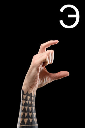 cropped view of male tattooed hand showing cyrillic letter, deaf and dumb language, isolated on black Reklamní fotografie