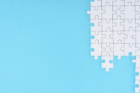 Flat lay with white puzzle pieces on blue background Stock Photo
