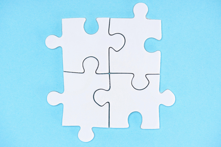 Top view of arranged white puzzle elements on blue backdrop Stock Photo