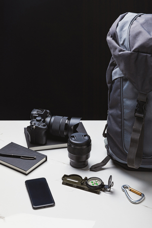 backpack, smartphone, photo camera with lens and tracking equipment