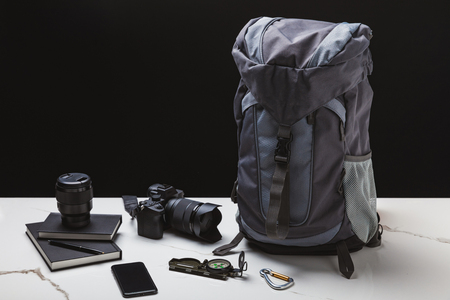 backpack, smartphone, compass, notebooks and photo camera with lens on black Stock Photo