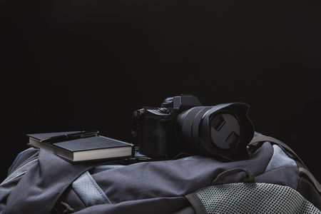 close-up view of photo camera with notebook and pen on backpack isolated on black Stock Photo