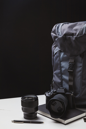 backpack, photo camera with lens and notebook with pen on black