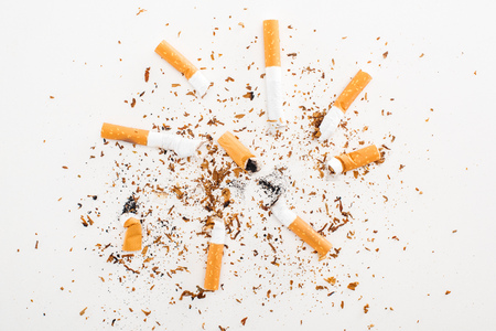 Studio shot of cigarette butts and tobacco isolated on white, stop smoking concept