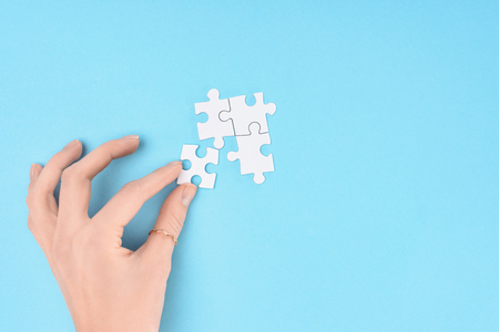 Partial view of woman with white puzzles pieces on blue background