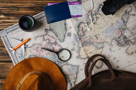 top view of brown leather bag, hat, magnifying glass, small model plane, earphones, photo camera, lens and passport with boarding pass on map