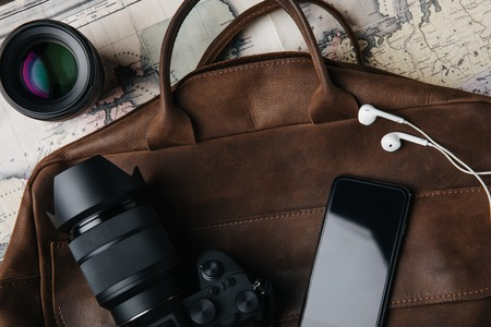 top view of brown leather bag with photo camera, lens, smartphone and earphones on map Zdjęcie Seryjne