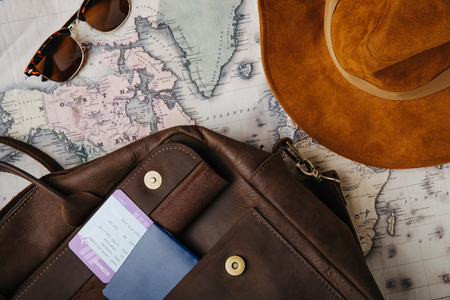 top view of leather bag, passport, ticket, sunglasses, hat and map