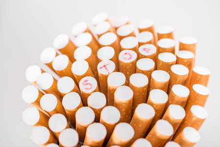 Studio shot of bunch of cigarettes isolated on grey, stop smoking concept