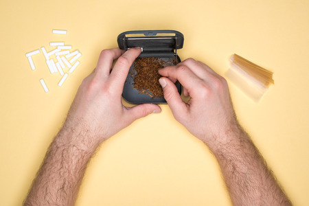 Cropped view of man using tobacco box isolated on yellow Stock Photo