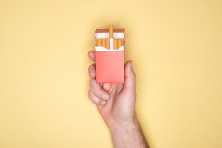 Cropped view of man holding red pack of cigarettes isolated on yellow