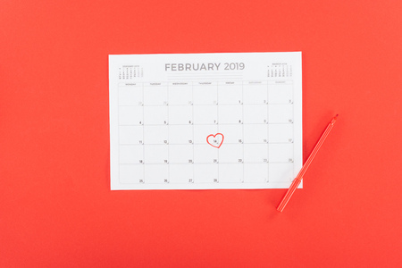 Top view of calendar with 14th February date marked with heart isolated on red, st valentines day concept Фото со стока