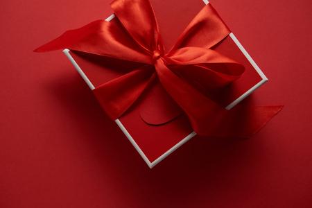 Vista superior de la caja de regalo roja con cinta de raso sobre fondo rojo.