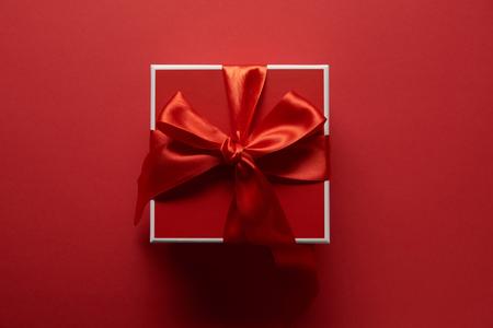 Vista superior del presente con cinta de seda sobre fondo rojo. Foto de archivo