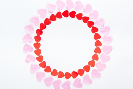 Top view of round frame made with red and pink paper hearts isolated on white, st valentines day concept