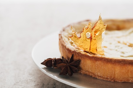 Close-up view of delicious flan cake with caramel and star anise on white plate