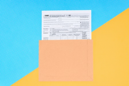 Top view of tax form on blue and yellow background with copy space Stockfoto