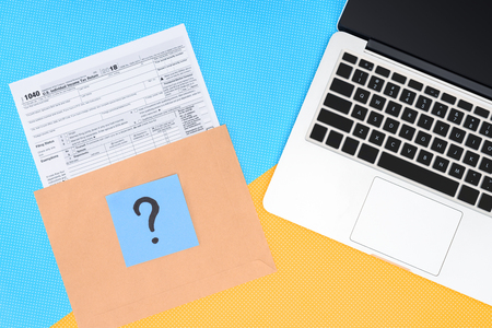 Top view of tax form, blue card with question mark and laptop on blue and yellow background