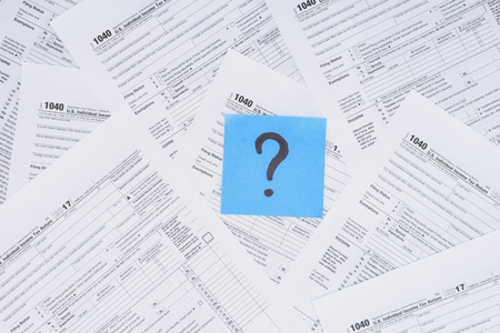 Top view of question mark on blue card with tax forms on background