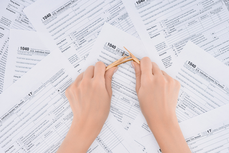 Cropped view of stressed woman breaking pencil with tax forms on background