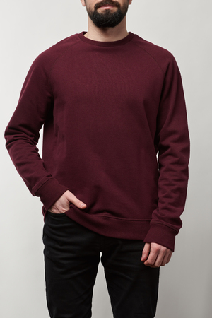 partial view of man in basic burgundy sweatshirt with copy space isolated on grey